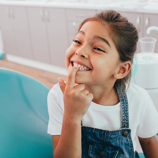 A little girl wearing denim overalls and pointing to her healthy teeth while at the dentist's office
