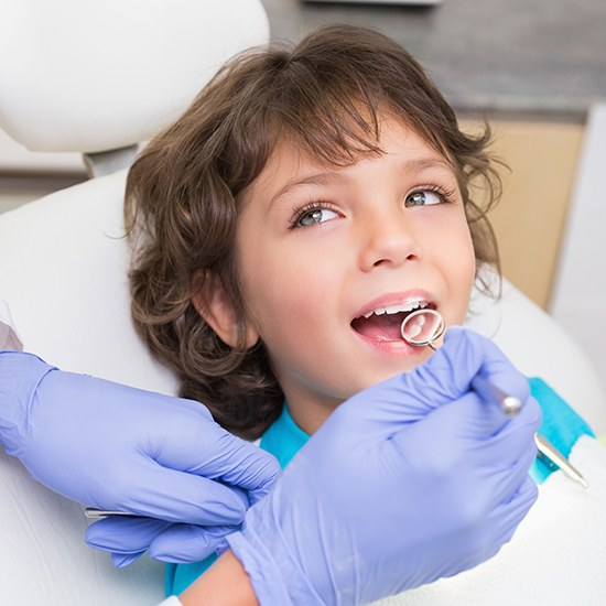 Dentist checking child's smile after fluoride treatment