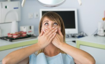 Fearful patient in need of sedation dentistry covering mouth